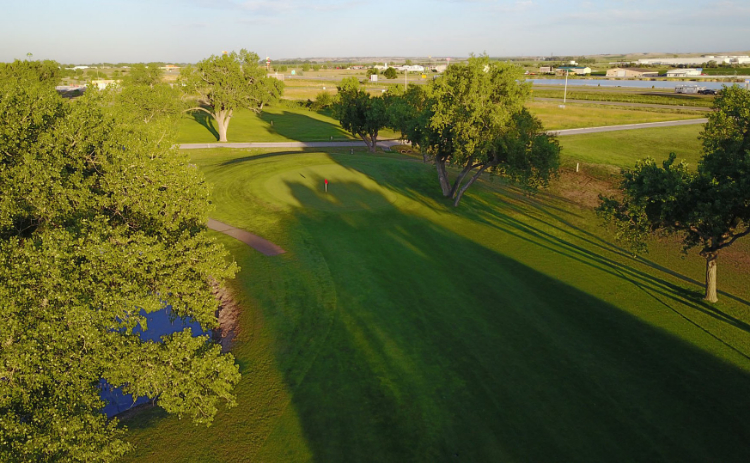 An aerial view of a pond next to a hole at Iron Eagle Golf Course