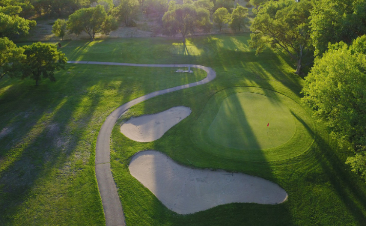 Aerial view of a cart path winding through Iron Eagle Golf Course